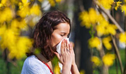 O tânără strănută într-un șervețel, aflându-se pe un câmp plin de flori sălbatice, cu un grad ridicat de polen
