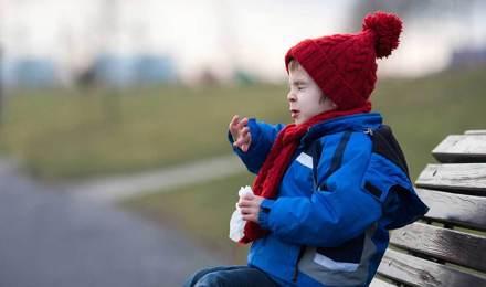 Un copil strănută pe o bancă în parc iarna