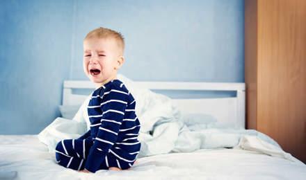 Un copil mic plângând pe un pat nefăcut