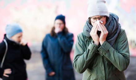 Една млада жена кихане, които може да искате някои дома средства за запушен нос