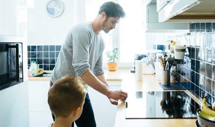 Muškarac čisti radnu površinu u kuhinji dok ga dijete pažljivo promatra