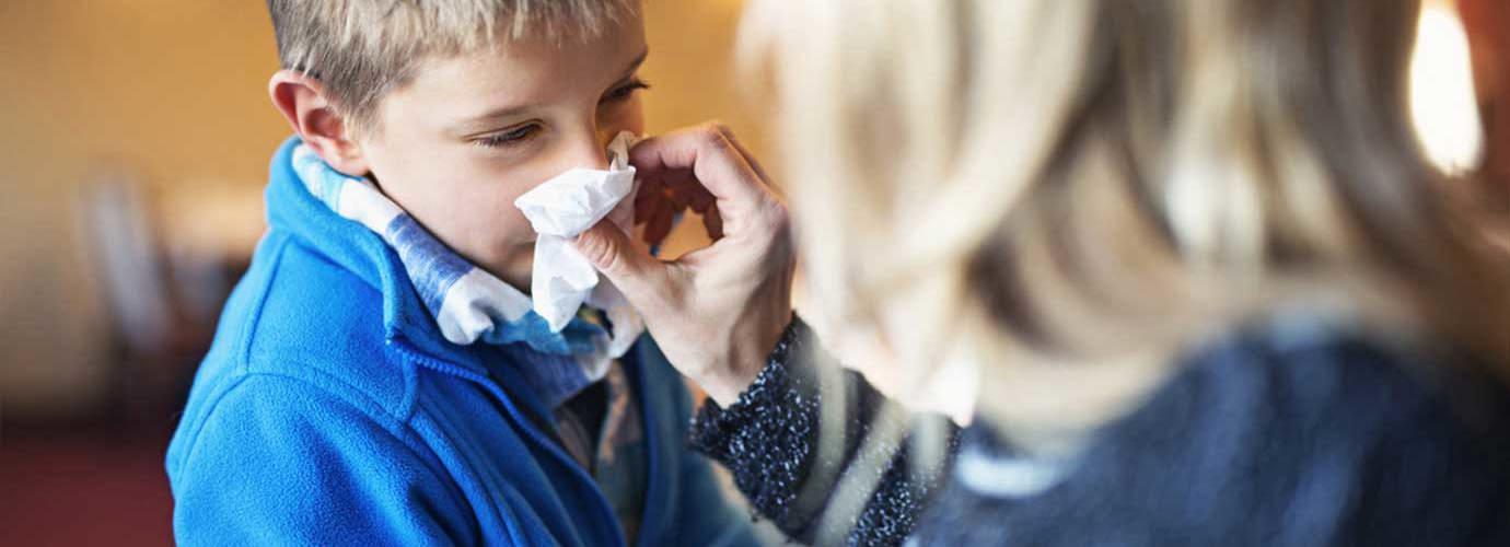 Maminka pomáhá svému dítěti se vysmrkat a při tom přemýšlí, jak zabránit dalšímu šíření nákazy