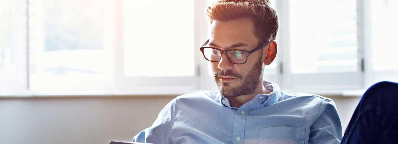 Muž s brýlemi a tabletem na pohovce