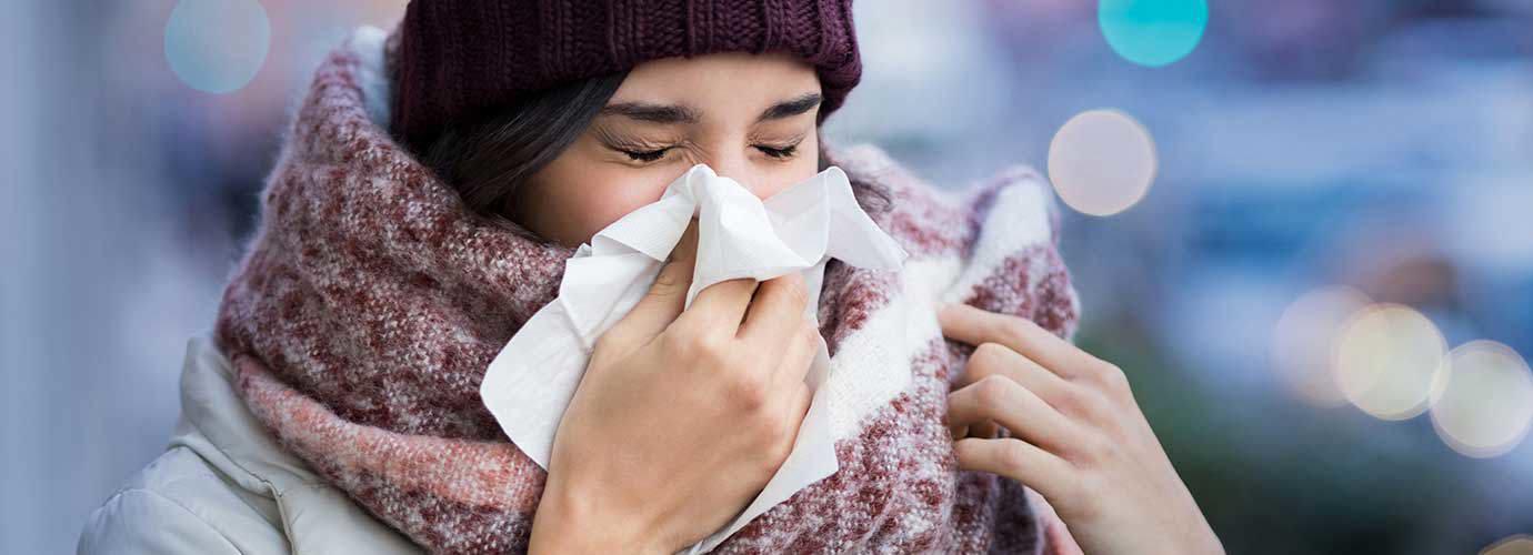 Žena zamotana u glomaznu zimsku odjeću boluje od simptoma sinusitisa i kiše u maramicu na otvorenom
