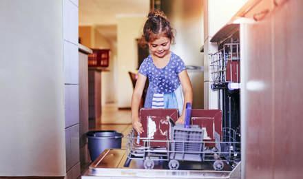 Holčička v kuchyni plní myčku
