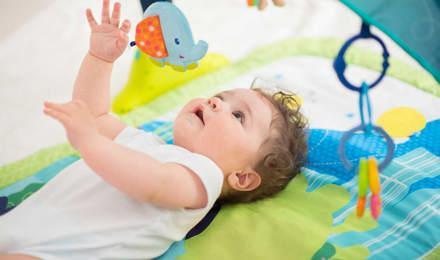 Dítě ležící na barevné podložce a hrající si s hračkami, které mu visí nad hlavou