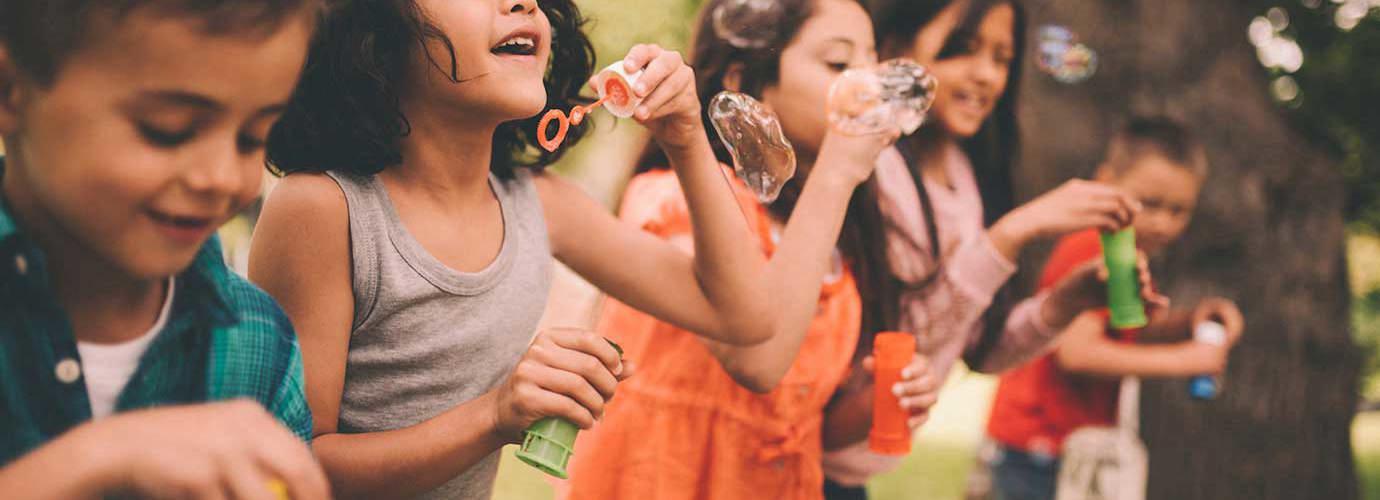 Léto a děti vyfukující bublifuky u dřevěného hrazení