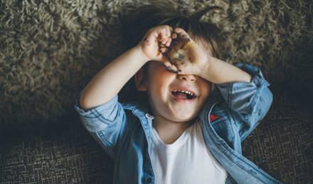 Malý kluk leží na podlaze, přikrývá si oči rukama a usmívá se do fotoaparátu