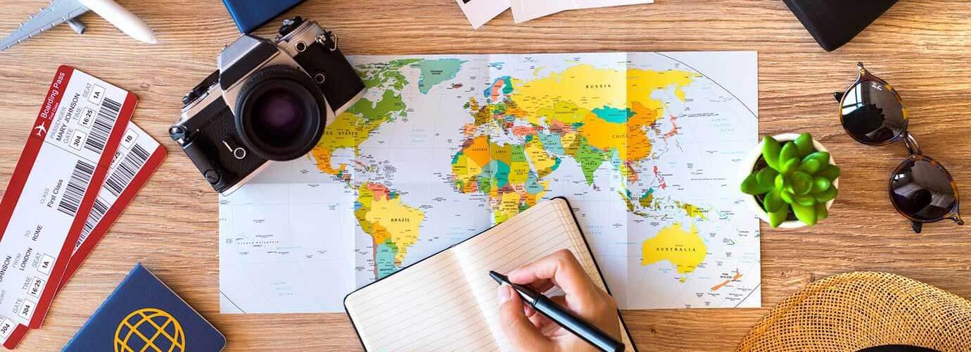 Stol s putovnicama, kartama, sunčanim naočalama, rokovnikom, avionskim kartama i bilježnicom za planiranje