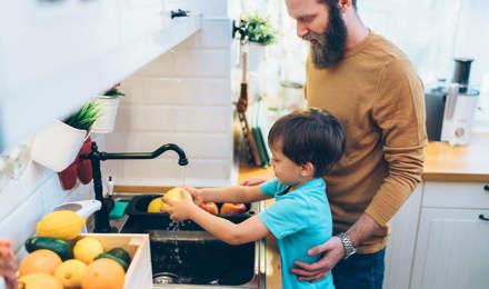 Μια μητέρα βοηθά τα παιδιά της να πλύνουν τα χέρια τους στην κουζίνα
