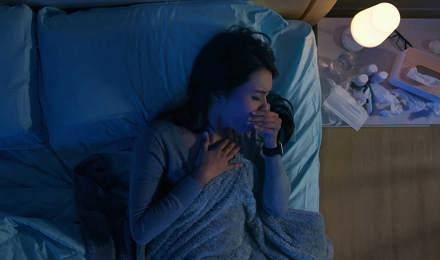 Μια γυναίκα στο κρεβάτι με βήχα δίπλα σε κομοδίνο με φάρμακα