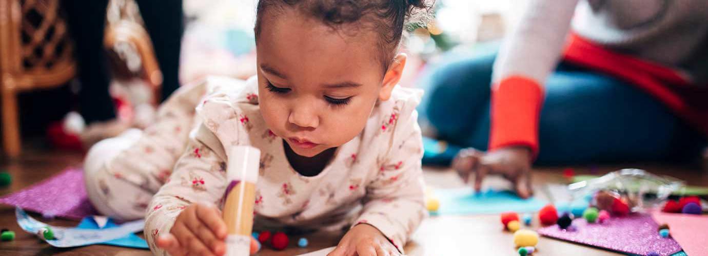 Ένα κορίτσι κρατάει κόλλα stick, ενώ κάνει χειροτεχνία