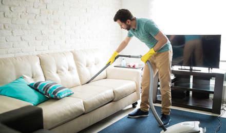 Ένας άντρας καθαρίζει έναν λευκό υφασμάτινο καναπέ με μια ηλεκτρική σκούπα
