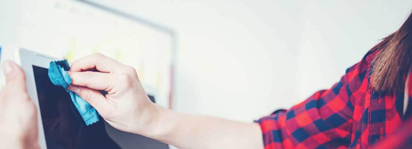 Μια γυναίκα καθαρίζει την οθόνη ενός κινητού ή ενός υπολογιστή
