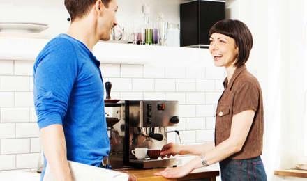 Μια γυναίκα χρησιμοποιεί μια καφετιέρα, ενώ μιλάει με έναν άντρα στην κουζίνα