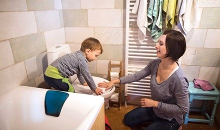 Μια μητέρα βοηθά τον γιο της να τραβήξει το καζανάκι