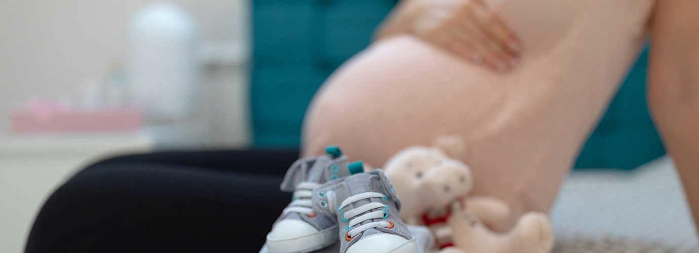 Μια τακτοποιημένη στοίβα μωρουδιακών ρούχων σε ένα κρεβάτι με μια έγκυο γυναίκα να φαίνεται στο παρασκήνιο