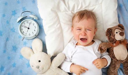Ένα μωρό πάνω σε μια κουβέρτα κλαίει ενώ περιβάλλεται από δύο λούτρινα παιχνίδια και ένα αναλογικό ξυπνητήρι