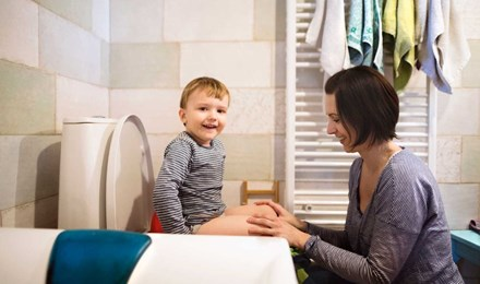 Μια μητέρα βοηθά τον γιο της να καθίσει στη λεκάνη της τουαλέτας