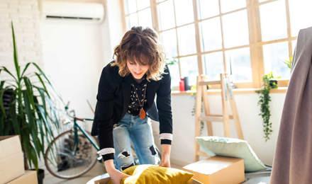 Μια γυναίκα κρατά μια κούτα ενώ τακτοποιεί και οργανώνει το σπίτι