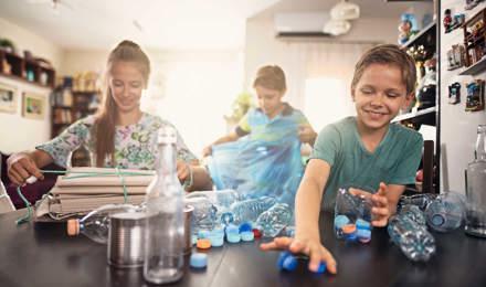 3 παιδιά προσπαθούν να καταλάβουν τι μπορούν να ανακυκλώσουν, βάζοντας διάφορα είδη πλαστικών σε κάδους στην κουζίνα