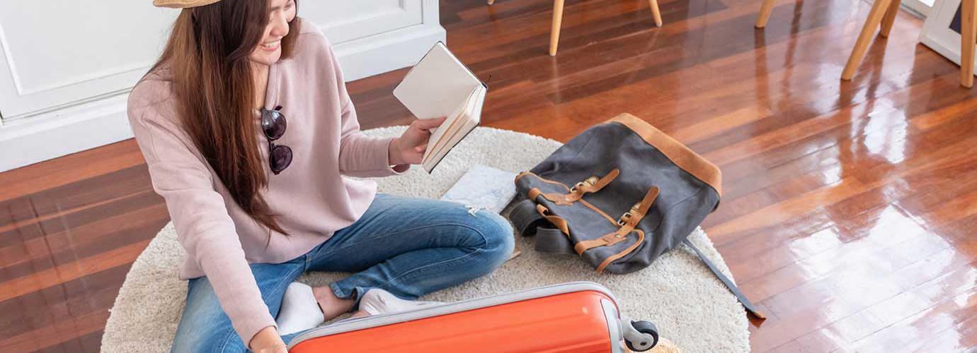 Μια νέα γυναίκα κάθεται στο πάτωμα και φτιάχνει τη βαλίτσα της για καλοκαιρινές διακοπές