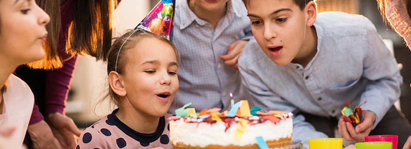 Παιδιά στέκονται γύρω από μια τούρτα σε ένα πάρτι γενεθλίων