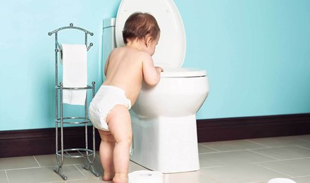Ein Kleinkind schaut in eine Toilette