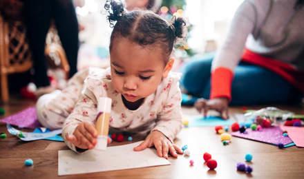 Ein kleines Mädchen hält einen Klebestift in der Hand und bastelt