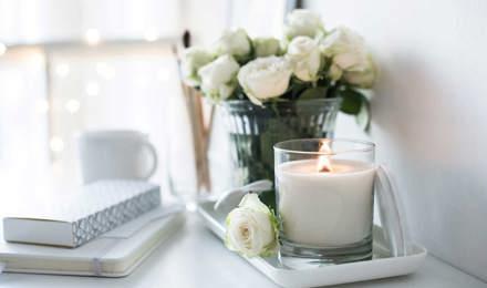 Eine handgemachte Kerze und Strauß Rosen auf einem Tisch