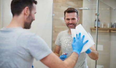 Eine Frau, die blaue Putzhandschuhe trägt, putzt einen Spiegel im Badezimmer