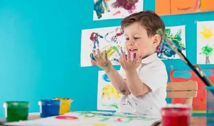 Ein Kind sitzt an einem Tisch und malt mit den Fingern