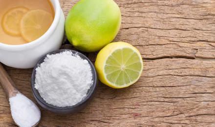 Eco freundliche Reinigungsmittel wie eine Zitrone, Limette und Backpulver auf einem hölzernen Schneidebrett