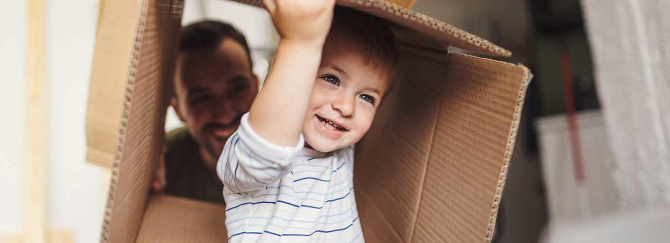 Ein kleiner Junge trägt eine Kiste während eines Umzugs aus einem Haus