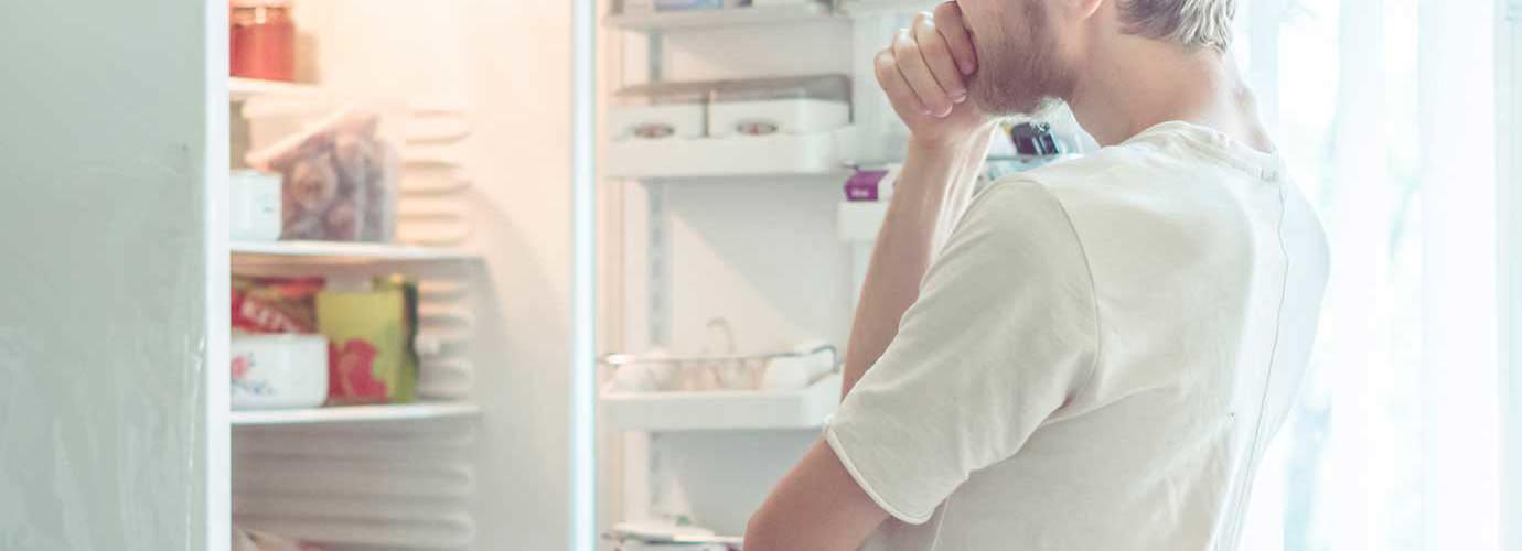 Ein Mann sucht nach Essen in einem Kühlschrank