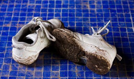 Брудні білі кросівки на блакитному кахельному фоні