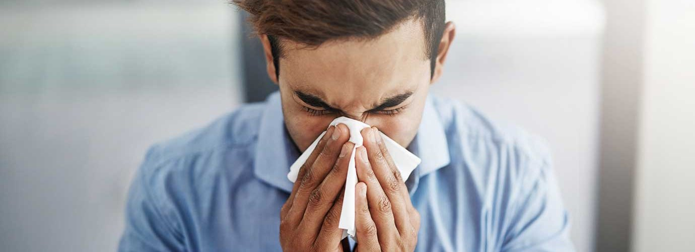 Млади човече кихане и духаше носа му с кърпичка