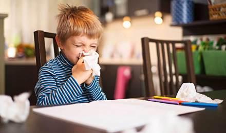 Молодий хлопець сякається, сидячи за столом з бавовняної тканини укладання навколо нього