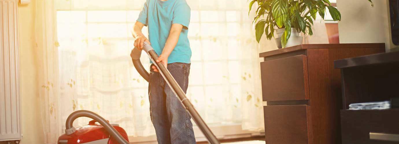 Хлопчик чистить килим пилососом