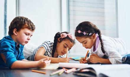 Tři děti si na podlaze kreslí pastelkami