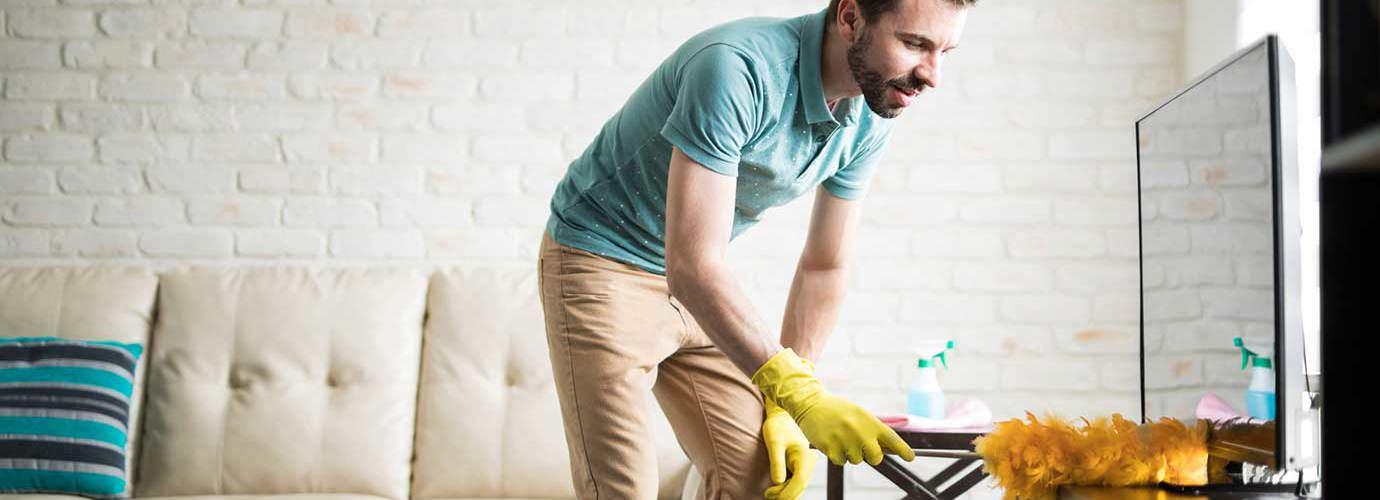 Muž při úklidu s prachovkou