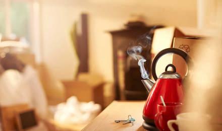 Červená kouřící konvice na kuchyňském pultu