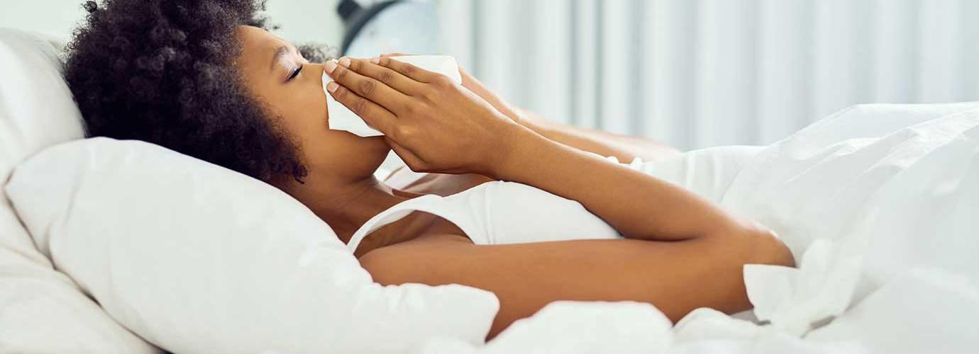 Молодая женщина в постели сморкается