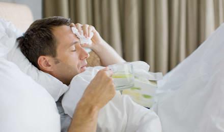 Больной человек в постели, держащий салфетку и чашку чая с лимоном