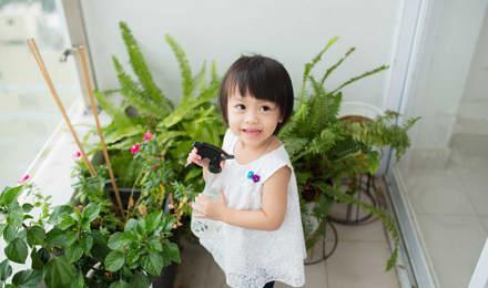 Маленькая девочка ухаживает за комнатными растениями