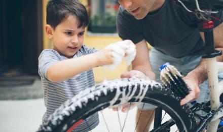 Отец и сын чистят велосипед