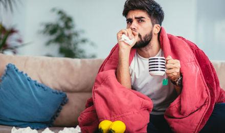 Молодой человек кашляет на диване под одеялом с кружкой чая и салфетками в руке