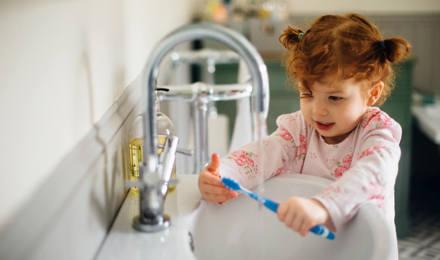 Мать помогает ее дочери и сыну мыть руки на кухне
