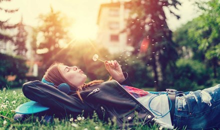Молодая женщина, лежа на траве, слушает музыку и дует на одуванчик