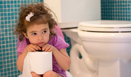 Маленькая девочка сидит на горшке и держит рулон туалетной бумаги в руках